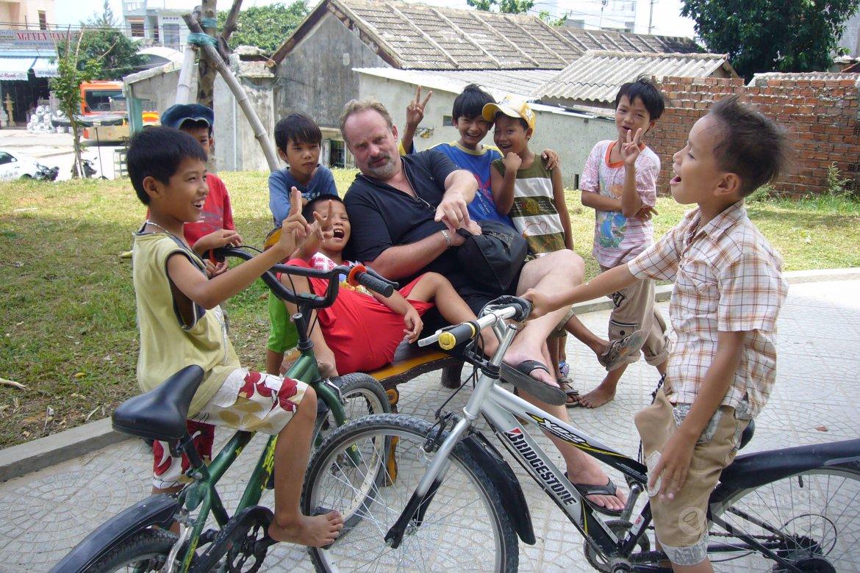 Kinderen uit de buurt komen kijken naar de clown die kan badmintonnen